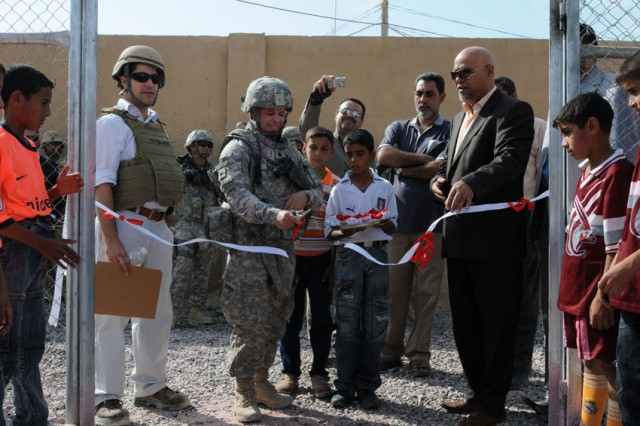 Flanked by children and leaders of Husayniyah, Lt. Col. Vince Rice, deputy team leader of the Karbala Provincial Reconstruction Team, cuts a ribbon to mark the official re-opening of the Husayniyah Youth Center. The center's basketball court, boxing ring and soccer field received makeovers.