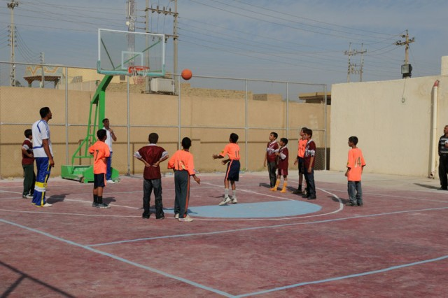 """Children play a game of basketball before the ribbon-cutting ceremony that marked the official re-opening of the Husayniyah Youth Center. The children received shoes and shirts from Soldiers of Troop A, 1st Squadron, 3rd Armored Cavalry Regiment immediately after the ceremony. """"We do our best to provide these things for the children because, in the end, they are the future of Iraq,"""" said Lt. Col. Vince Rice, deputy team leader of the Karbala Provincial Reconstruction Team."""