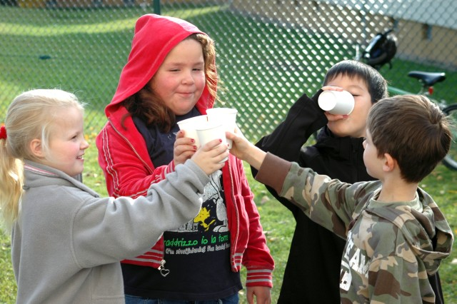 Hunter Savell (from left), Lillie del Rio and Phillip Dodson toast the fruits of their labor while Joshua Nielson gets right to sampling the freshly squeezed apple juice at Aukamm Elementary School.