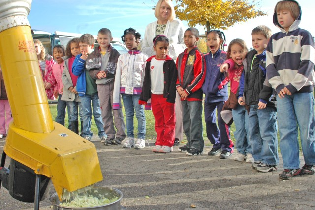 Aukamm Elementary School students watch as the apples they selected and washed are mulched in a shredder before being pressed and then turned into apple juice.