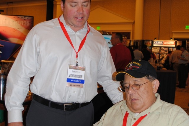Chris Seagren and Henry Dahan (seated) of a service-disabled veteran-owned small business look at business cards from several interested agencies they met at the 2010 National Veteran Small Business Conference and Expo in Las Vegas.