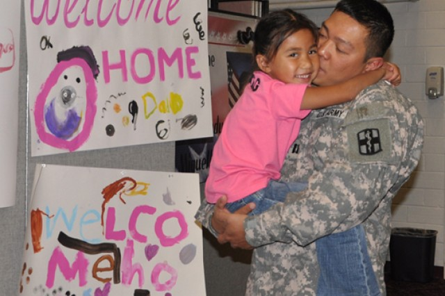 Capt. Francisco Gumataotao, commander of the 418th Medical Logistics Company, kisses his 5-year-old daughter, Tasi, after she shows him the welcome-home signs she made for him after a ceremony held Nov. 4 at Army Community Service.