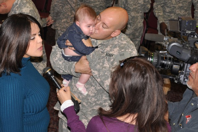 Staff Sgt. Roberto Figueroa holds his 4-month-old daughter, Gabriela, as he and his wife, Elizabeth are interviewed by one of several local reporters attending the welcome-home ceremony Nov.4 at Army Community Service.