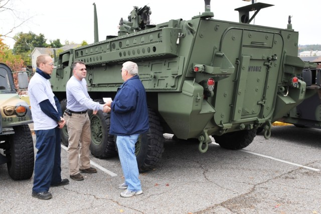Anniston Army Depot retiree and Gadsden resident Donald Morgan talked about his 30-plus years of depot experience with mechanics Jeremy Smith and Neil Chandler beside the Stryker on display outside the convention hall at the Nov. 3 Patriots Day Program.