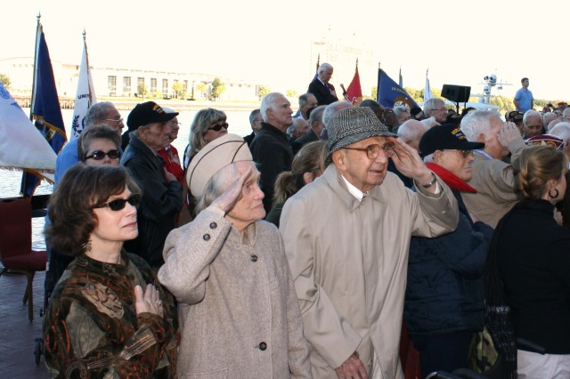 Pam Allen (left) stands with her mother, 90-year-old Genevieve Rhodes, and father, 92-year-old Walter Rhodes, as they salute the colors during the World War II memorial ceremony Nov. 7 on River Street in Savannah. Walter salutes with his left arm since he's recovering from a broken right shoulder.