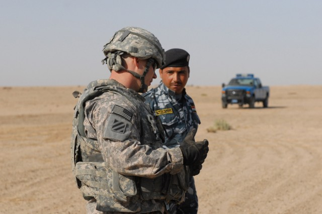 Staff Sergeant Brendan Carey (left), with the 442nd MP Co., 4th AAB, 3rd ID, advises an Iraqi Police officer on evasive driving tactics during a class in Anbar province, Iraq, Oct. 30.