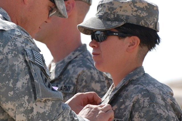 Colonel Roger Cloutier, commander of 1st AAB, 3rd ID, USD-C awards Spc. Angela Marino, a motor transport operator assigned to F Co., TF 3/69 Armor, 1st AAB, 3rd ID, USD-C, and a Dothan, Ala., native, a Purple Heart for wounds the Soldier received in action, Aug. 18.