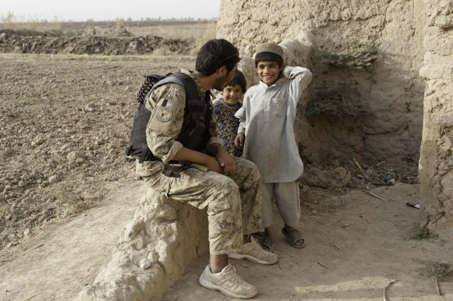 Afghan children chat with Mir Abdel, a policeman with 2nd Battalion, 3rd Afghan National Civil Order Police Brigade, during an afternoon patrol Oct. 29, 2010, with U.S. Special Forces in Zhari district, Kandahar province.