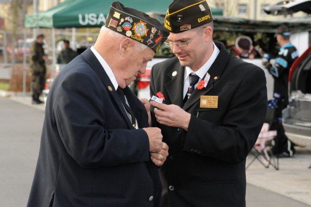 Two members of the Veterans of Foreign Wars Post 10692 attached flowers to their lapels during the Veterans Day activities in Grafenwoehr, Germany, Nov. 11, 2010.