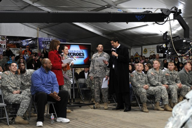 ESPN anchors Hannah Storm and Josh Elliot get ready to present the Sportscenter Top 10 Plays with members of the 18th Combat Sustainment Support Battalion during the live Veterans Day broadcast in Grafenwoehr, Germany, Nov. 11, 2010.