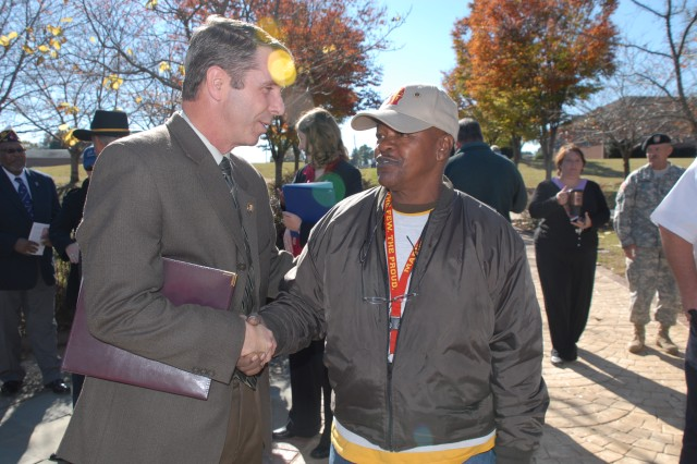 Fort A.P. Hill employee, Warren Hill, converses with U.S. Representative Rob Wittman during the installation\'s Veterans Day observance held Nov. 9, 2010.