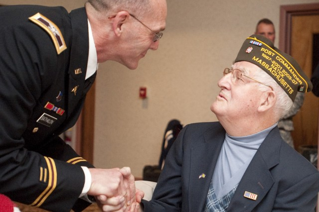 Col. Gaston Bathalon, commander of the U.S. Army Research Institute of Environmental Medicine, hands a coin from Brig. Gen. Harold Greene, NSSC commander, to World War II veteran Harry K. Seaholm at a Veterans' Appreciation Dinner.
