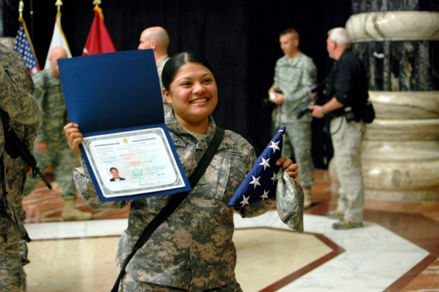 Pfc. Sandra Colocho, Enhanced Combat Aviation Brigade, 1st Infantry Division, holds her certificate of citizenship and a U.S. flag, Nov. 11, after becoming a naturalized citizen in a ceremony at the Al-Faw Palace on Camp Victory, Iraq. Colocho came to the U.S. from El Salvador when she was 11 months old, and she is now serving as her unit's supply clerk. (U.S. Army photo by Spc. Roland Hale, eCAB, 1st Inf. Div. PAO)