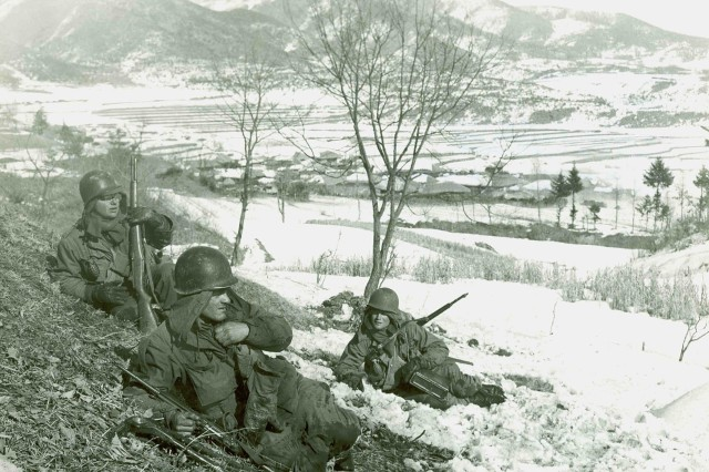 American Soldiers rest on a hillside during a cold winter somewhere in Korea late 1950-early 1951.  The Soldiers have little in the way of cold weather equipment for fighting in temperatures that often fell below freezing.