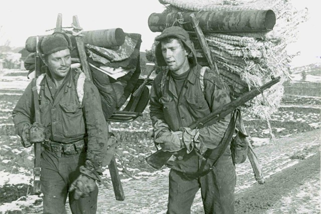 American Soldiers SFC Carl W. Howard (left) and PFC Danel Wellman, members of the 25th Infantry Division, use Korean methods for transporting supplies to the front in early 1951.  The extreme cold made transportation unreliable, and often supplies had to be brought up on foot by the men themselves.