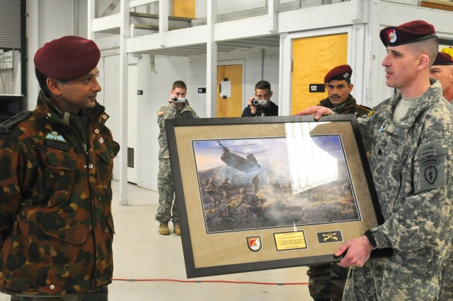 Lt. Col. Christopher J. Cassibry, commander of 1st Squadron (Airborne), 40th Cavalry Regiment, 4th Brigade Combat Team (Airborne), 25th Infantry Division, presents a gift to a leader from the Indian army during an airborne jump wing exchange ceremony Nov. 13 at Joint Base Elmendorf-Richardson, Alaska. The Soldiers earned their foreign jump wings Nov. 10 when they conducted a combined jump during exercise Yudh Abhyas 2010.