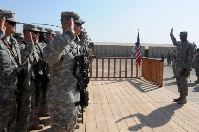 BABIL PROVINCE, Iraq - Maj. Gen. Vincent K. Brooks, United States Division-South commander, administers the Oath of Enlistment to reenlistees at Contingency Operating Site Kalsu Nov. 11, 2010. The ceremony was part of a mass reenlistment held to honor Veterans Day.