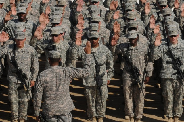 Reenlistees of the 3rd Armored Cavalry Regiment raise their hands to recite the Oath of Enlistment administered by Maj. Gen. Vincent K. Brooks, United States Division-South commander, on Contingency Operating Site Kalsu Nov. 11, 2010. A mass reenlistment ceremony that spanned all three of the regiment's bases was conducted to honor Veterans Day.