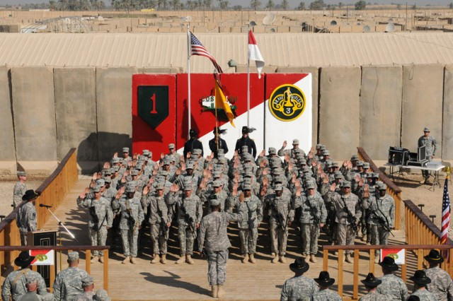 Reenlistees of the 3rd Armored Cavalry Regiment raise their hands to recite the Oath of Enlistment administered by Maj. Gen. Vincent K. Brooks, United States Division-South commander on Contingency Operating Site Kalsu Nov. 11, 2010. A mass reenlistment ceremony that spanned all three of the regiment's bases was conducted to honor Veterans Day.