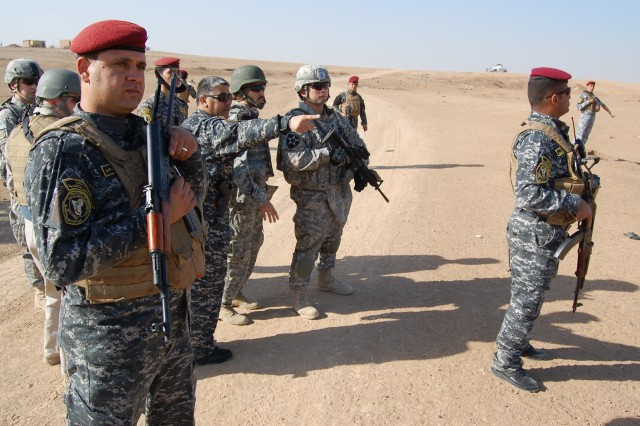 CONTINGENCY OPERATING SITE MAREZ, Iraq -Col. Sa'ad Banaiean Abied (center), commander of the Mosul Federal Police, shows Soldiers assigned to Task Force Spear, 4th Advise and Assist Brigade, 1st Cavalry Division, the progress during a cordon and search mission Nov. 11. The Task Force Spear troopers advise on criminal investigative tactics to enhance the Iraqis' ability to plan and conduct future operations.