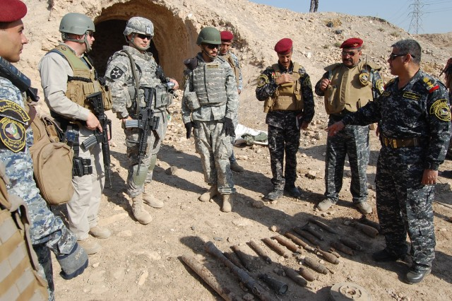 CONTINGENCY OPERATING SITE MAREZ, Iraq -Iraqi Federal Police in Mosul display explosives found during a cordon and search mission to Soldiers assigned to Task Force Spear, 4th Advise and Assist Brigade, 1st Cavalry Division, Nov. 11. The U.S. Soldiers provide security and assistance during missions, assessing the Iraqi's operations and tactics, in support of Operation New Dawn.