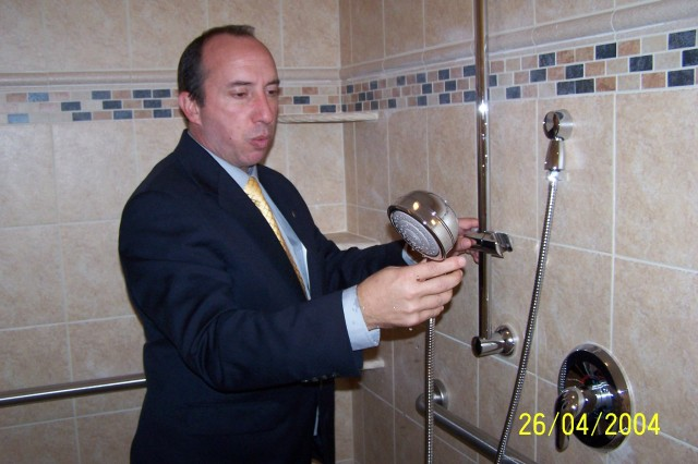 John Gonsalves, president and founder of Homes for Our Troops, demonstrates the wheelchair-accessible shower in the home his organization donated to Capt. Ferris Butler on Veterans Day.