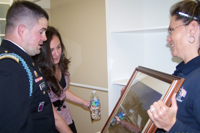 "In their handicap-accessible walk-in closet, retired Capt. Ferris Butler and his wife Laura accept a framed photo from Doreen Lewis, field operations manager of Homes for Our Troops.  The photo shows members of the ""Building Brigade"" assembled on the roof and in front of their adaptive house."