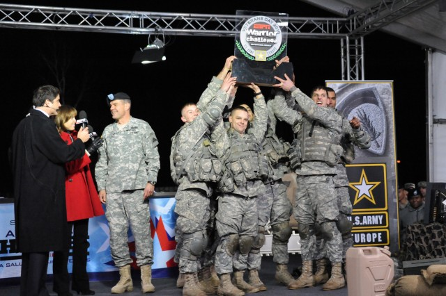 Members of the 172nd Separate Infantry Brigade hoist their trophy after winning the ESPN Warrior Challenge, part of the ESPN SportsCenter broadcast at Grafenwoehr, Germany. To the left of the winning Soldiers are ESPN anchors Hannah Storm and Josh Elliot and the commanding general of the Joint Multinational Training Command Brig. Gen. Steven L. Salazar.