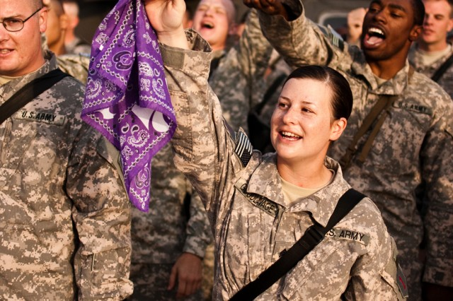"""Sgt. Amanda Goodlavage, a native of Manhattan, Kan., waves a K-State flag in the air Aug. 22, during a partnership pep rally on Camp Taji, Iraq. Soldiers on Camp Taji serving with the Enhanced Combat Aviation Brigade, 1st Infantry Division, an aviation unit from Fort Riley, Kan., gathered on the camp's flight line to take part in the filming of the """"Wabash Cannonball,"""" a traditional college dance, for a video highlighting the partnership between K-State and Fort Riley. K-State graduates 2nd Lt. Chance Moyer and 1st Lt. Jerimiah Wood led the troops in the dance. (U.S. Army photo by Spc. Roland Hale, eCAB, 1st Inf. Div. PAO)"""