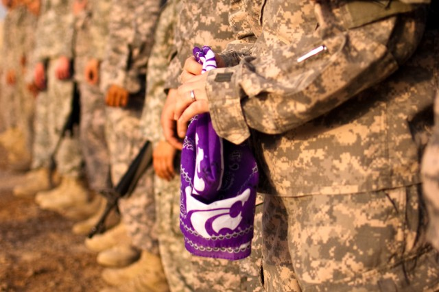 A Soldier serving in Iraq with the Enhanced Combat Aviation Brigade, 1st Infantry Division, an Army brigade from Fort Riley, Kan., holds a K-State banner during a partnership pep rally on Camp Taji, Iraq, Aug. 22. (U.S. Army photo by Spc. Roland Hale, eCAB, 1st Inf. Div. PAO)
