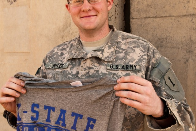 Second Lt. Chance Moyer, a K-State graduate serving in Iraq with the Enhanced Combat Aviation Brigade, 1st Infantry Division, holds up one of his favorite pieces of Wildcat football gear. Moyer is a native of Chanute, Kan., and deployed to Iraq shortly after graduating from K-State in 2009. (U.S. Army photo by Spc. Roland Hale, eCAB, 1st Inf. Div. PAO)