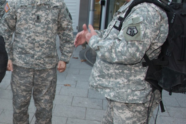 Staff Sgt. Joel H. Trammell Jr., the noncommissioned officer in charge of the 88th Chaplain Detachment, 7th Warrior Training Brigade, 7th Civil Support Command, describes his experiences to Command Sgt. Maj. Michael E. Biere, the command sergeant major of the 7th CSC, upon returning to Ramstein Air Base, Germany, Nov. 2 after a nine month deployment to Iraq to augment the 1st Infantry Division in support of Operation Iraqi Freedom. Trammell, a native of Chicago, Ill., and a chaplain's assistant, was awarded an Army Commendation Medal and a Navy and Marine Corps Commendation Medal for his performance.