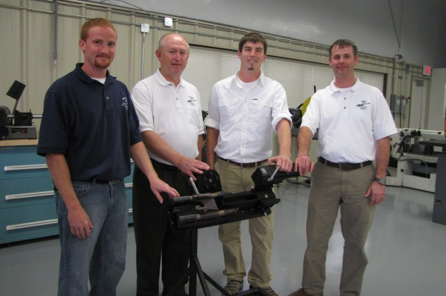 Machinists, from left, Brett Lewis, Tim Simmons, Ryan Stewart and Ben Rice are proud of the role they've had in the development of the Kiowa Warrior's M2P machine gun mount. The machinists designed the prototype for the first mount and are now working on prototyping mount revisions, such as the mount shown in the foreground with them.
