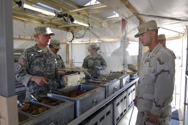 FORT IRWIN, Calif.- Pottsville, Pa., native Spc. Joseph Roshannon of Headquarters and Headquarters Troop, Regimental Support Squadron, 11th Armored Cavalry Regiment, serves food to a Soldier during the Department of the Army-level Phillip A. Connelly Cup Competition, at the National Training  Center on Fort Irwin, Calif., Nov. 3. The field kitchen team won the U.S. Army Forces Command of the competition and was awarded for their efforts during an awards presentation ceremony at Fort Irwin, Nov. 12. Results from the DA-level competition will be announced in early December. (Photo by Sgt. Giancarlo Casem, 11th ACR Public Affairs)