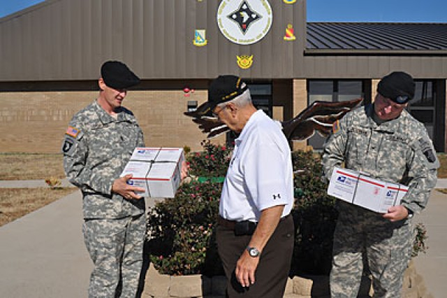 Bill Owens, retiree, hands off boxes of his homemade treats to Col. Michael Peterman and Command Sgt. Maj, David Thompson. This particular delivery is intended for Maj.Gen. John F. Campbell, 101st Airborne Division and Combined Joint Task Force - 101 commander, and Gen. David Petraeus, International Security Assistance Force commander.