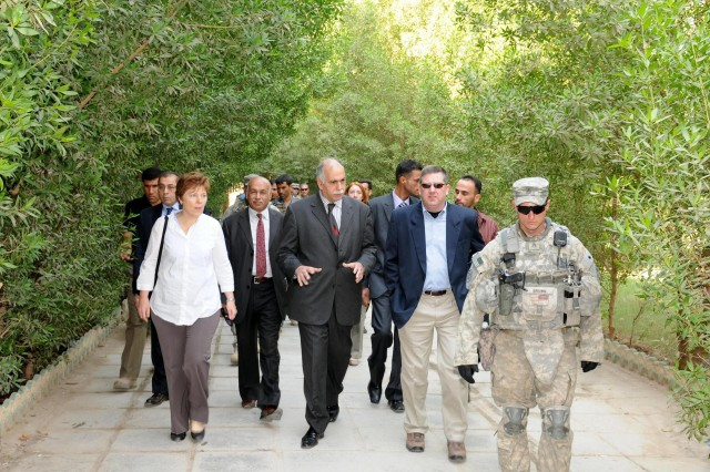 Saleh Ismail Najim (center), the chancellor of the University of Basra, talks with Kirk Schulz (right), Kansas State University president, and Barbara Leaf, Basra Provincial Reconstruction Team leader, while walking through a courtyard at the University of Basra Nov. 9. Representatives from KSU, Basra PRT and United States Division-South met with university staff to discuss issues surrounding Iraq's higher education system.