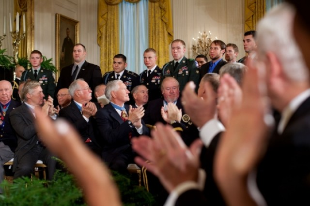 President Barack Obama, former Medal of Honor winners, and other people in the audience recognize members of U.S. Army Staff Sgt. Salvatore Giunta's unit during Giunta's Medal of Honor presentation ceremony in the East Room of the White House, November 16, 2010.