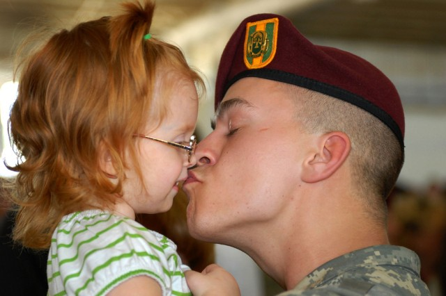 Spc. Andy Cogswell, a military police with the 65th Military Police Company, kisses his daughter for the first time in 15 months at Green Ramp on Pope Air Force Base. The company of 160 Soldiers was welcomed home by family and friends after a 15-month deployment in Iraq.