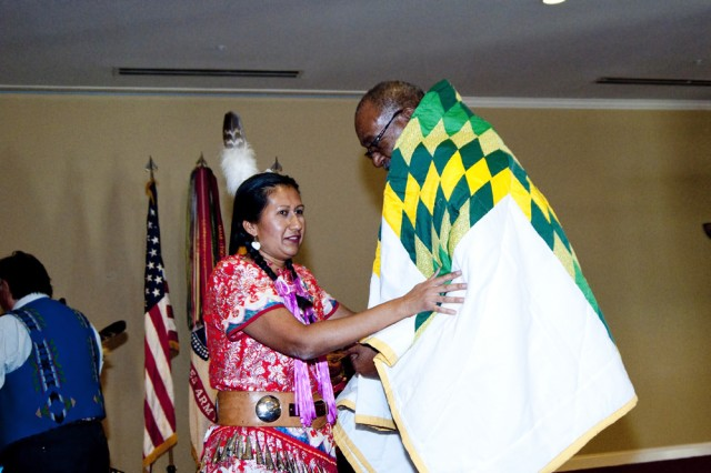 Ms. Lupe Lopez from the Red Boy Productions Native American dance group presents Fort Irwin/National Training Center EEO Director Mr. John Winkfield a quilt made by members of the Olalla Sioux tribe in North Dakota for his efforts in raising awareness of Native American culture and heritage on Nov. 16, 2010.