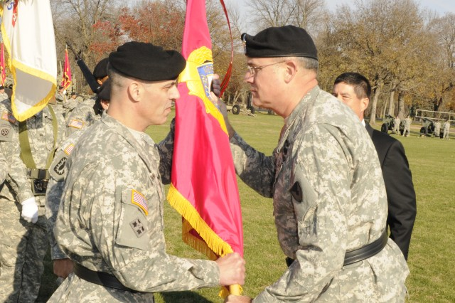 Brig. Gen. Gustave F. Perna, new commander of the Joint Munitions Command, receives the JMC flag from Lt. Gen. James H. Pillsbury, deputy commander, U.S. Army Materiel Command, during the JMC Assumption of Command ceremony, Nov. 16, on the Rock Island Arsenal, Ill.