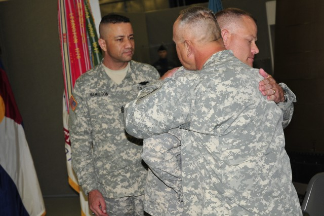 Command Sgt. Maj. Joseph Rhodes hugs Col. Greg Bowen, commander of the 100th Missile Defense Brigade, after the Change of Responsibility ceremony at Peterson Air Force Base Nov. 1 in Colorado Springs, Colo.  During the ceremony, Rhodes was celebrated for his 34 years of service as he retired.