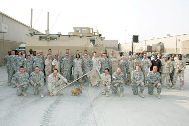 Ricky, right side with brown shirt, stands with fellow Soldiers and civilians in Southwest Asia.