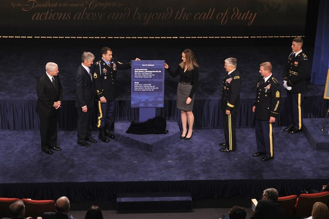 Medal of Honor recipient Staff Sgt. Salvatore A. Giunta and his wife, Jennifer, unveil the Hall of Heroes Plaque in the Pentagon Auditorium on Nov. 17, 2010.