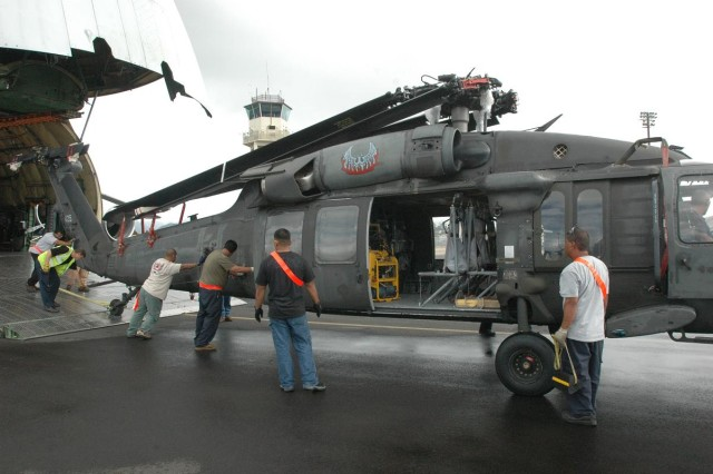 A crew of URS Corporation civilian contractors unloads a UH-60 Black Hawk helicopter, arriving from Ft. Drum, N.Y., from the belly of an airplane at Hickam Air Force Base, Nov. 1. The aircraft arrived from Ft. Drum, N.Y., and were later transported by 25th Combat Aviation Brigade Soldiers to Wheeler Army Airfield.  (Photo by Sgt. 1st Class Tyrone C. Marshall Jr.  25th Combat Aviation Brigade Public Affairs)