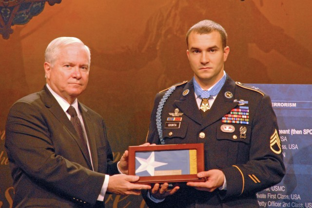"""Secretary of Defense Robert M. Gates presents Staff Sgt. Salvatore """"Sal"""" Giunta with a Medal of Honor flag during a Hall of Heroes ceremony at the Pentagon Nov. 17. Giunta is the first living, Active Duty servicemember in a generation to be inducted into the hallowed chamber, which is reserved for recipients of the nation's highest award for valor in combat."""