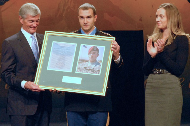 """Secretary of the Army John McHugh presents Staff Sgt. Salvatore """"Sal"""" Giunta with a framed copy of Giunta's Medal of Honor citation for his actions in the Korengal Valley, Afghanistan, during a Hall of Heroes ceremony at the Pentagon Nov. 17 while Giunta's wife Jennifer looks on. On Oct. 25, 2007, Giunta single-handedly rescued a wounded buddy from being kidnapped by two enemy fighters."""