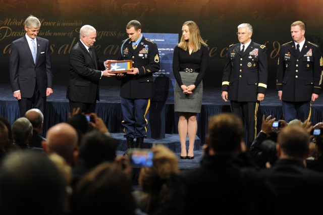 Defense Secretary Robert M. Gates presents the Medal of Honor flag to Medal of Honor recipient Army Staff Sgt. Salvatore Giunta during the soldier's induction into the Hall of Heroes at the Pentagon, Nov. 17, 2010.