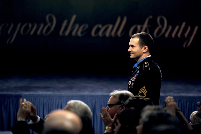Medal of Honor recipient Army Staff Sgt. Salvatore Giunta looks over at his team members from Company B, 2nd Battalion, Airborne, 503rd Infantry Regiment, as they stand to be recognized during Giunta's induction ceremony into the Hall of Heroes at the Pentagon, Nov. 17, 2010.