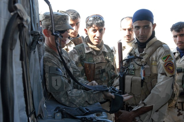 Specialist Brandon Pate, with the General Support Aviation Battalion, 1st Infantry Division, United States Division - Center, teaches 12 Iraqi Army Soldiers with the 7th IA Division how to fasten a seatbelt on a UH-6 Black Hawk helicopter properly Nov. 11 during an air assault operations class at Camp Mejid, Iraq.