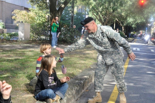Command Sergeant Major Jeffrey Ashmen, 3rd ID command sergeant major, pauses along the parade route during the Savannah Veterans Day parade to give high-five to a child watching 3rd ID Soldiers march down the Spanish moss-lined city streets, Nov. 11.